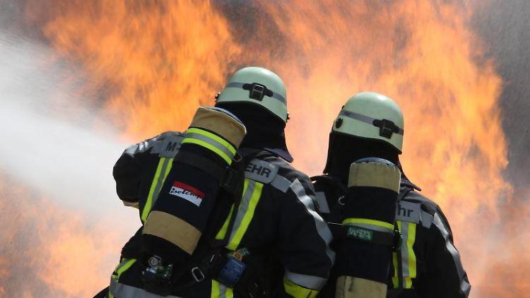 Zwei Feuerwehrmänner führen Löscharbeiten an einer Simulationsanlage durch. Foto: Stephan Jansen/dpa