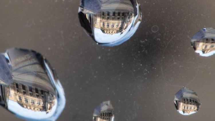 Regentropfen auf einem Rückspiegel eines Autos. Foto: Robert Michael/dpa-Zentralbild/dpa
