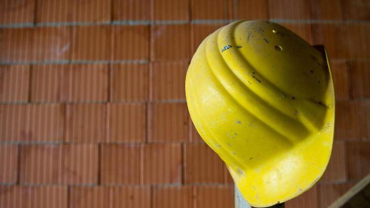 Ein Bauhelm hängt auf einer Baustelle. Foto: Daniel Bockwoldt/dpa