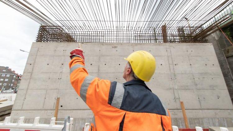 Ein Bauarbeiter der Deutschen Bahn (DB) steht vor einem neuen Brückenteil. Foto: Friso Gentsch/dpa