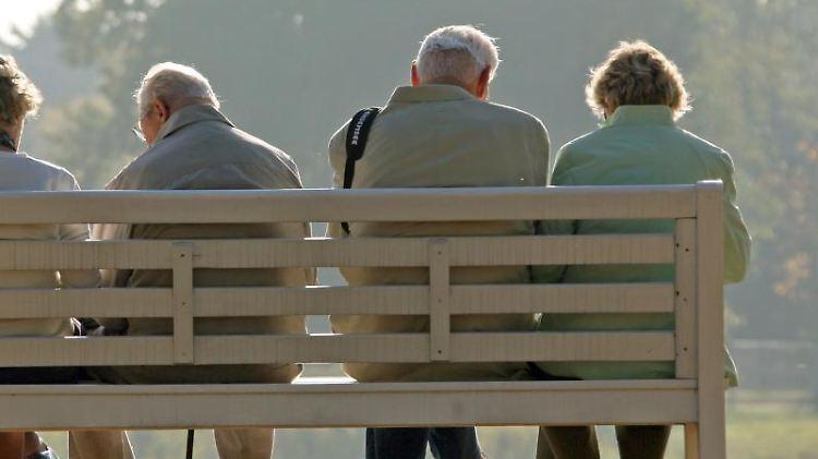 Rentner sitzen auf einer Parkbank. Foto: Ralf Hirschberger/zb/dpa