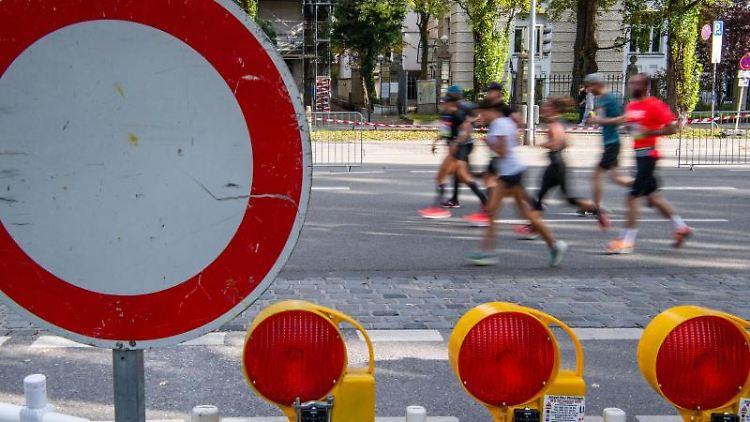 Marathonteilnehmer beim Generali München Marathon auf der gesperrten Leopoldstraße. F. Foto: Lino Mirgeler/dpa