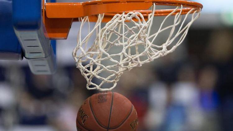 Ein Basketball geht in den Korb. Foto: Lukas Schulze/dpa