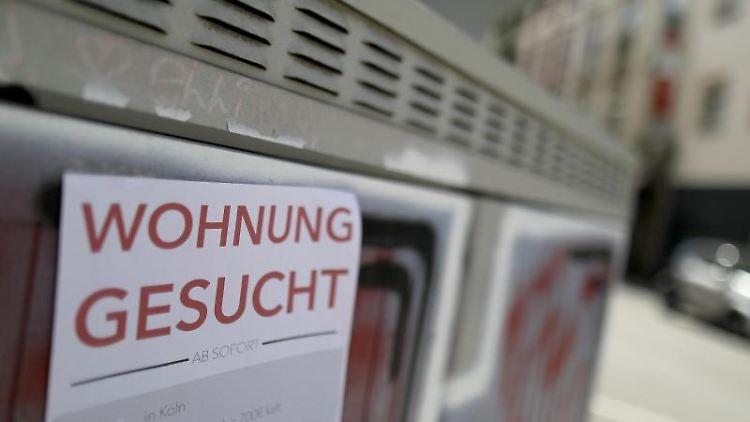 Mit einem Zettel an einer Hauswand suchen Menschen eine Wohnung. Foto: Oliver Berg/dpa