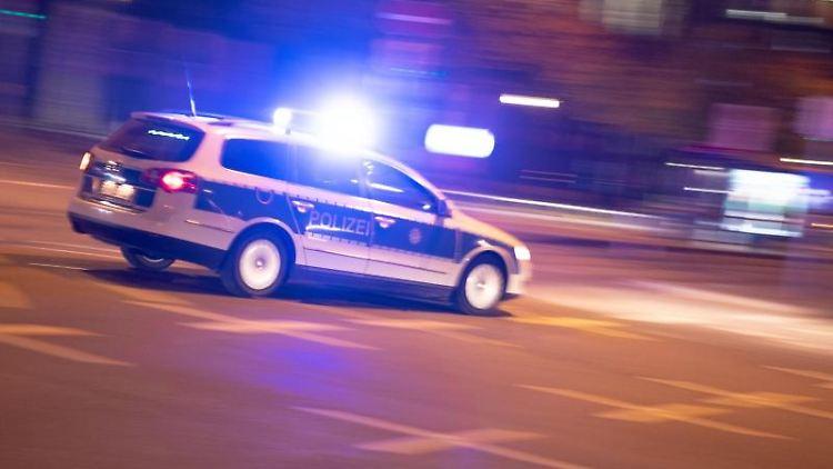 Ein Polizeiauto fährt unter Einsatz von Blaulicht und Sirene eine Straße entlang. F. Foto: Lino Mirgeler/dpa