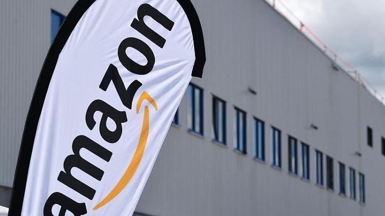 Ein Amazon-Banner weht vor dem Amazon Verteilzentrum. Foto: Martin Schutt/zb/dpa/Archivbild