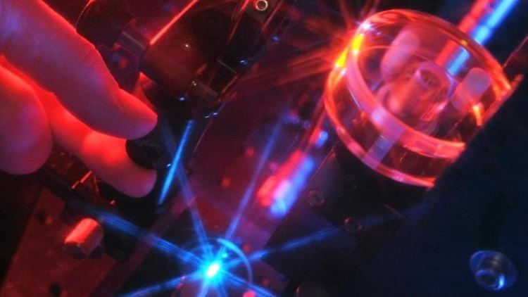 Eine Person führt ein Experiment durch, bei dem mit Hilfe vcn Laserlicht Wasserstoff erzeugt wird. Foto: Jan-Peter Kasper/dpa-Zentralbild/dpa/Archivbild