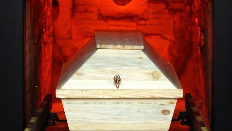 Ein Sarg wird im Krematorium in einen Ofen gefahren. Foto: Kay Nietfeld/dpa/Archivbild