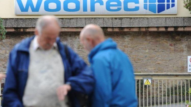 Zwei Männer vor der Zufahrt zum Woolrec-Firmengelände. Foto: Arne Dedert/dpa/Archivbild