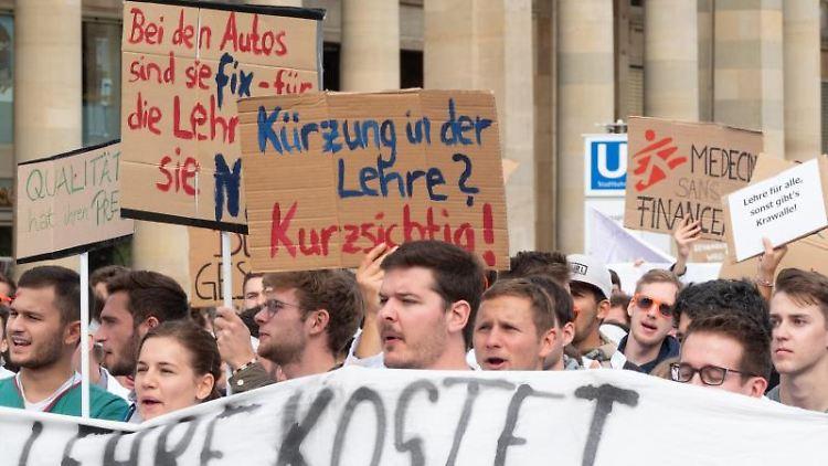 Demonstranten halten Protestschilder hoch. Foto: Gregor Bauernfeind/dpa