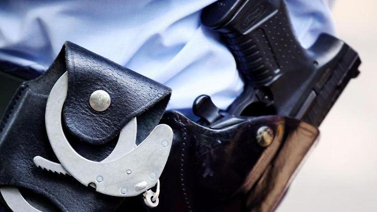 Ein Polizist mit Handschellen und Pistole am Gürtel. Foto: Oliver Berg/dpa