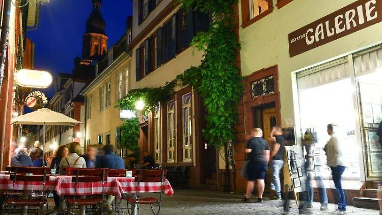 Besucher stehen in der Altstadt von Heidelberg. Foto: Uwe Anspach/dpa/Archivbild
