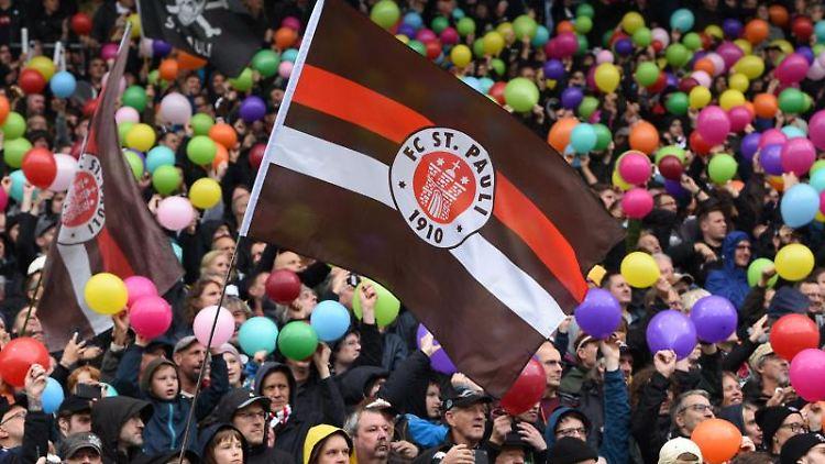 Hamburgs Fans schwenken eine Fahne und halten Luftballons. Foto: Daniel Bockwoldt/dpa/Archivbild