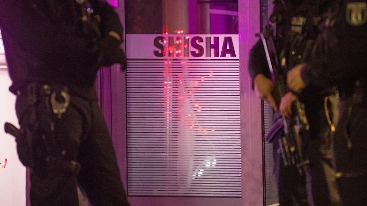 Beamte von Polizei und Zoll führen in einer Shisha-Bar eine Polizeikontrolle durch. Foto: Jörg Carstensen/dpa/Archivbild