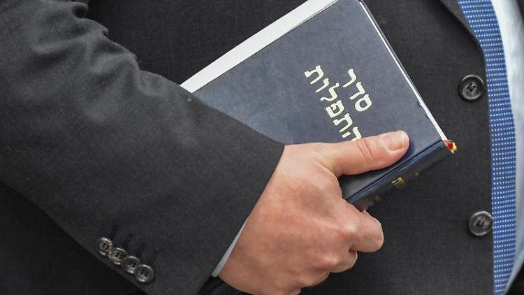 Ein Rabbi hält ein jüdisches Gebetsbuch in seiner Hand. Foto: Patrick Pleul/dpa-Zentralbild/dpa/Archivbild