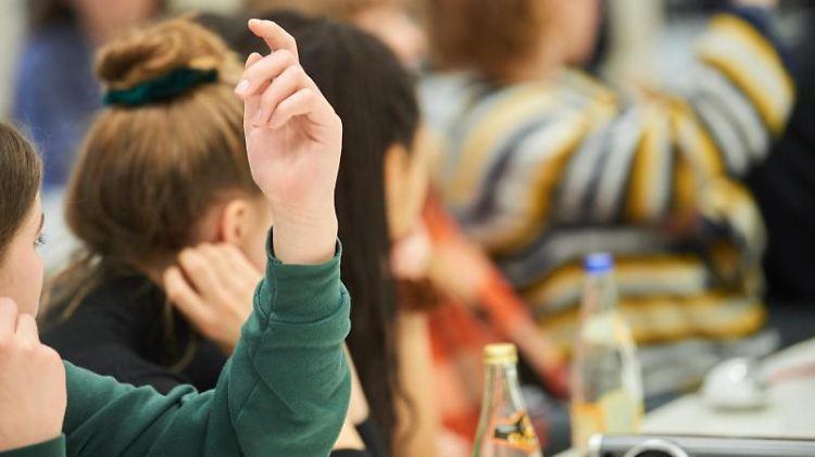Zwei Schülerinnen melden sich im Unterricht. Foto: Annette Riedl/dpa/Archivbild
