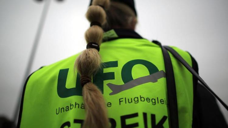 Eine Flugbegleiterin in einer Warnjacke zum Streik der Gewerkschaft Ufo. Foto: Oliver Berg/dpa