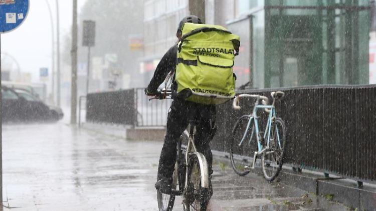 Bei starkem Regen fährt ein Fahrradkurier auf einem Radweg. Foto: Bodo Marks/Archivbild