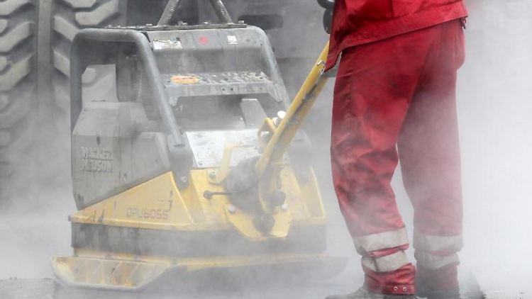 Bauarbeiter reparieren eine Straßendecke. Foto: Roland Weihrauch/dpa/Archivbild