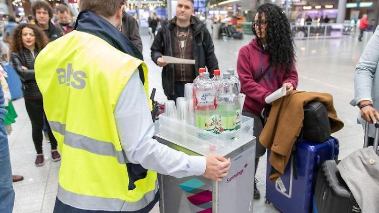 Ein Mitarbeiter verteilt Getränke und gibt Informationen an gestrandete Fluggäste. Foto: Friso Gentsch/dpa