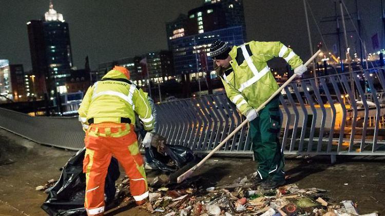 Mitarbeiter einer Reinigungsfirma räumen Müll im Hafen weg. Foto: Daniel Bockwoldt/Archiv