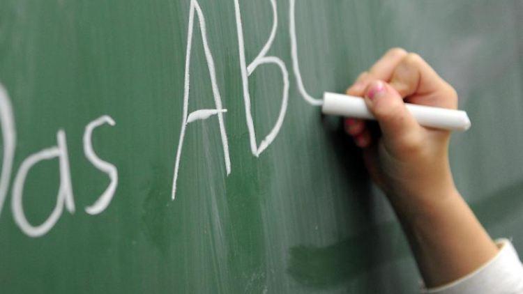 Eine Schülerin der zweiten Klasse schreibt das ABC an die Tafel. Foto: Daniel Reinhardt/Archiv