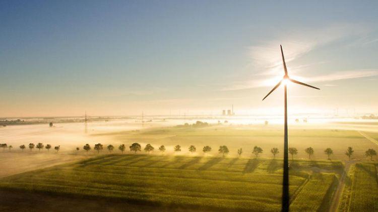 Nebelschwaden ziehen im Licht der aufgehenden Sonne über Felder mit einem Windrad. Foto: Julian Stratenschulte/dpa