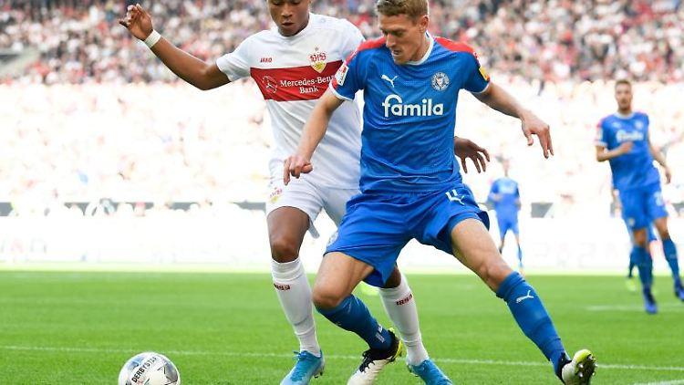 Roberto Massimo vom VfB Stuttgart und Johannes van den Bergh von Holstein Kiel (l-r.) in Aktion. Foto: Tom Weller/dpa