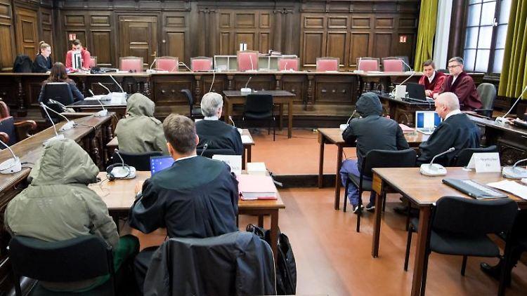 Drei Angeklagte sitzen im Landgericht im Saal neben ihren Anwälten. Foto: Daniel Bockwoldt/dpa pool/dpa