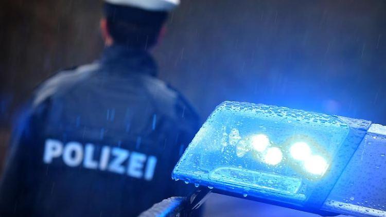 Ein Polizist steht im Regen vor einem Streifenwagen mit Blaulicht. Foto: Karl-Josef Hildenbrand/dpa