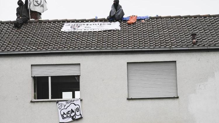 Zwei Aktivisten sitzen auf dem Dach einer ehemaligen Polizeiwache. Foto: Patrick Seeger/dpa