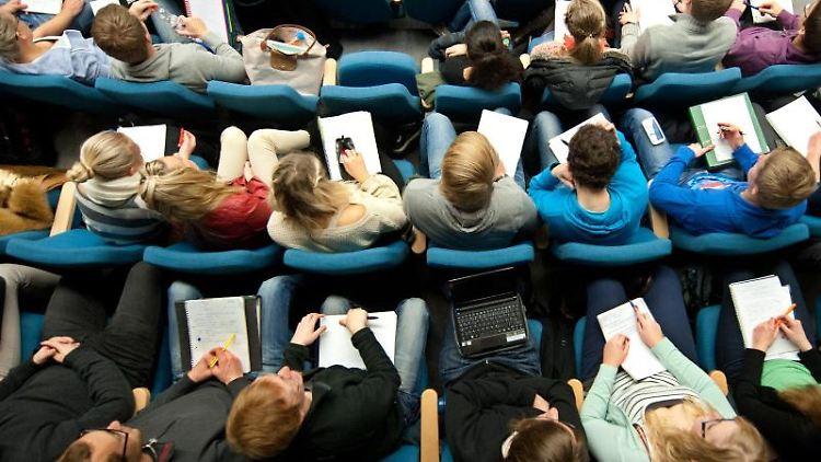 Studenten sitzen in einer Vorlesung in einem Hörsaal. Foto: Julian Stratenschulte/dpa
