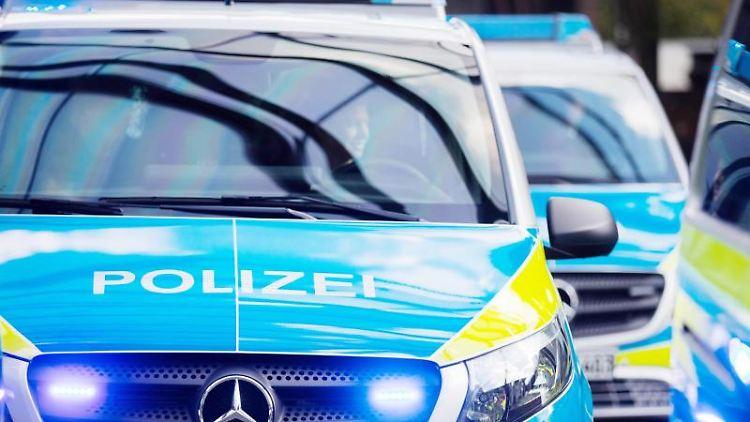 Polizeiwagen mit Blaulicht fahren auf einer Straße. Foto: Rolf Vennenbernd/dpa