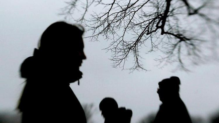 Passanten stehen neben einem Baum. Foto: Julian Stratenschulte/dpa/Archivbild