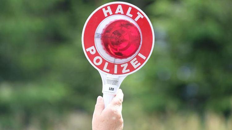 Eine Polizistin hält eine Winkerkelle in die Höhe. Foto: Sebastian Willnow/zb/dpa