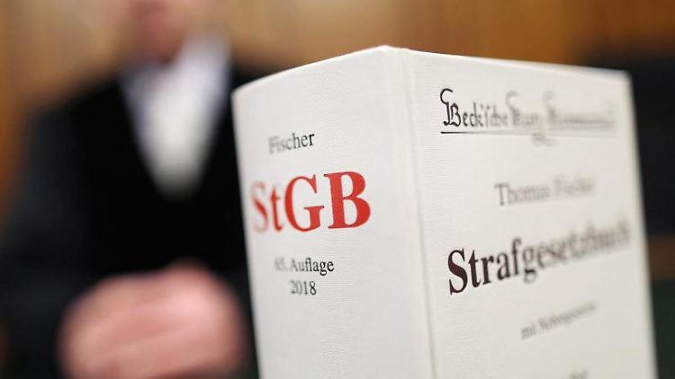 Ein Strafgesetzbuch (StGB) steht in einem Gericht auf der Richterbank. Foto: Oliver Berg/dpa/Archivbild