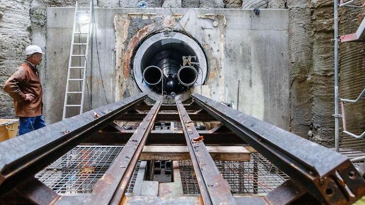 Ein Rohrleitungsbauer steht in einem Schacht am Anfang eines Medientunnels. Foto: Markus Scholz/dpa