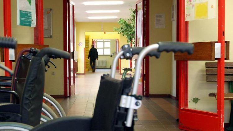 Rollstühle stehen vor einer Brandschutztür in einer Werkstatt für behinderte Menschen. Foto: Felix Frieler/dpa/Archivbild