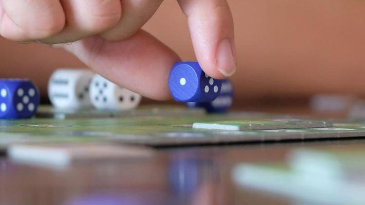 Ein Spielefan hält an einem Tisch einen Würfel über einem Spielbrett. Foto: Sebastian Willnow/zb/dpa/Archivbild