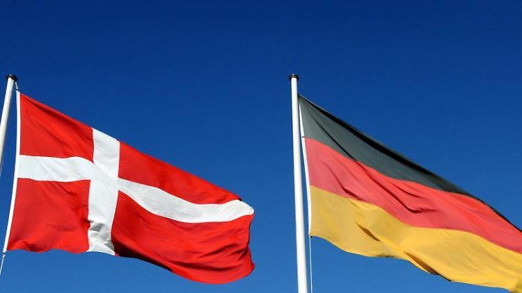 Die deutsche und die dänische Flagge wehen vor blauem Himmel. Foto: Carsten Rehder/dpa/Archivbild