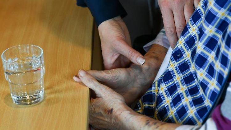 Eine Pflegerin hilft einer alten Frau, die an einem Tisch vor einem Glas Wasser sitzt. Foto: Jens Kalaene/zb/dpa
