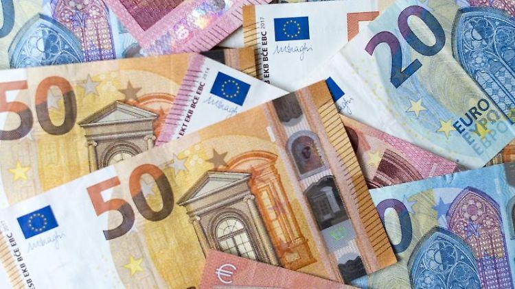 Verschiedene Banknoten liegen auf einem Haufen. Foto: Monika Skolimowska/zb/dpa/Archivbild