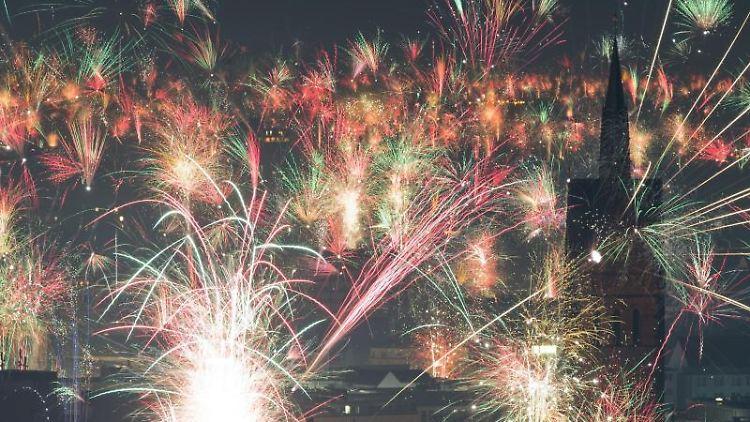 Feuerwerk explodiert kurz nach Mitternacht am Nachthimmel. Foto: Julian Stratenschulte/dpa/Archivbild