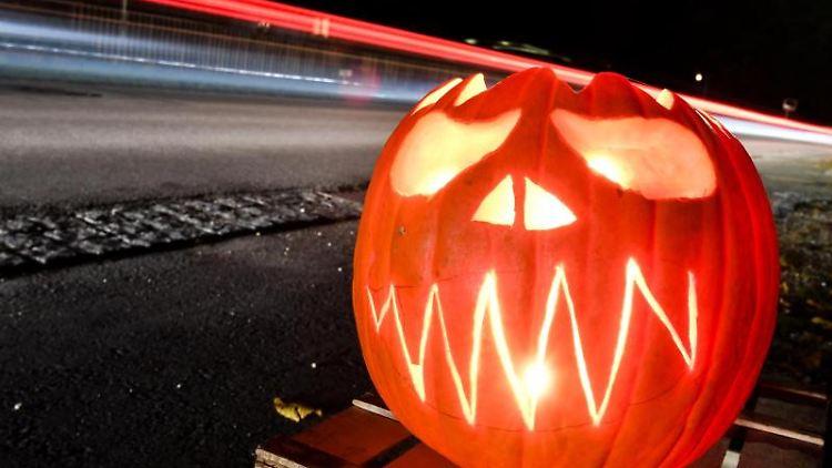 Ein beleuchteter und geschnitzter Halloween-Kürbis mit Geister-Motiv steht am Straßenrand. Foto: Felix Kästle/dpa/Archivbild