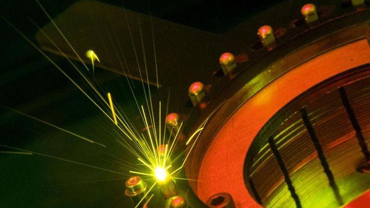 Ein Laser einer Maschine des Maschinenbauers Trumpf schweißt Metallstifte. Foto: Marijan Murat/dpa/Archivbild