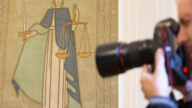 Ein Fotograf vor dem Bild der Justitia. Foto: Friso Gentsch/dpa/Symbolbild