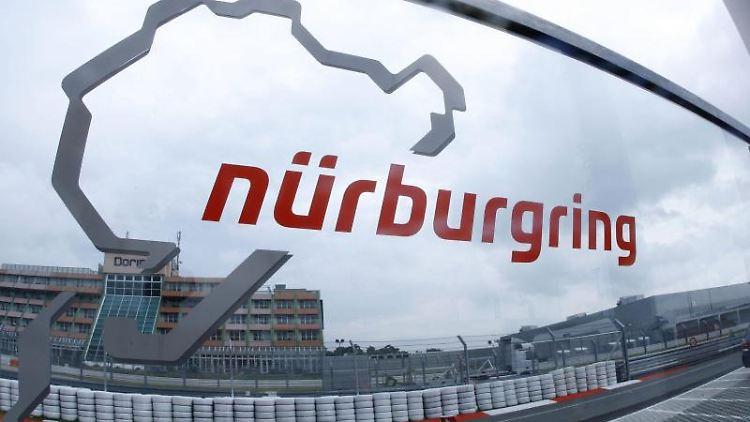 Eine Glasscheibe mit dem Logo der Rennstrecke Nürburgring steht an der Zufahrt zur Rennstrecke. Foto: Jens Büttner/dpa/Archivbild