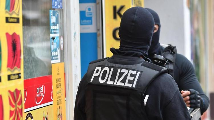 Vermummte Einsatzkräfte stehen vor einem Kiosk im Stadtteil Neukölln. Foto: Paul Zinken/dpa/Archivbild