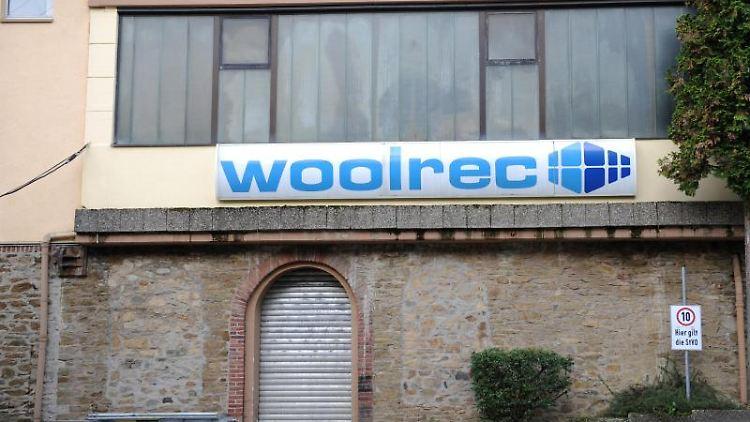 Ein Firmenschild auf einem Gebäude der Firma Woolrec. Foto: Arne Dedert/dpa/Archivbild