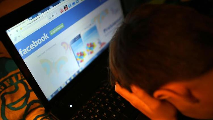 Ein Junge reibt sich am vor seinem Laptop beim Betrachten der Facebook-Seite die Augen. Foto: Oliver Berg/dpa/Archivbild